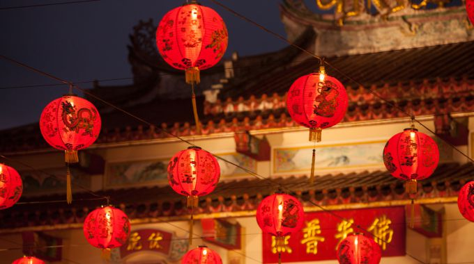 Red Chinese lantern in front of Chinese temple.
